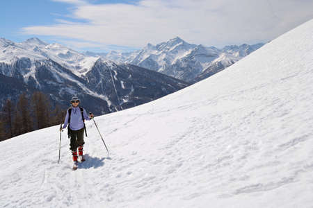 Tour skier hiking uphill under a bright sun in spring  photo