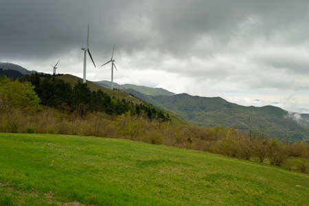 Electrical power generating wind turbines on the Maritime Alps  Italy  with storm cloud in the sky  photo