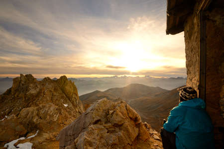Hiker sitting near hut and looking at a stunning sunset from the summit of rocky and barren mountains in the italian - french western Alps  great view over Massif des Ecrins majestic peaks   Stock Photo