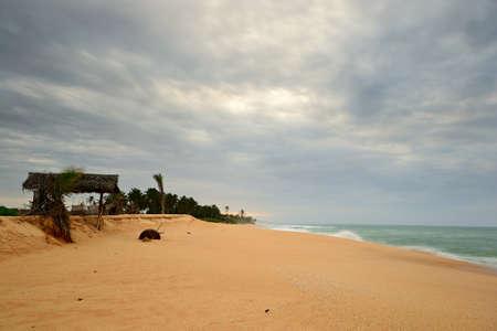 Beach hut damaged by monsoon on tropical desert beach at dusk