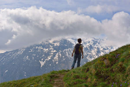 Female hiker with backpack walking in the italian Alps  Stock Photo