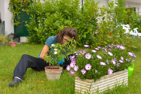 Woman taking care of flowers and plants in home garden. photo