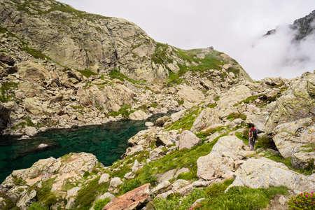 Female hiker walking near wonderful green blue alpine lake on rocky landscape  photo