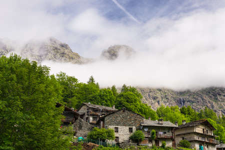 Small group of old stone houses between mountain and forest in the italian Alps  photo