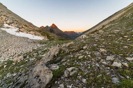 Warm red light at sunrise glowing the highest peaks of the italian - french Alps  Little basic hut for accomodation