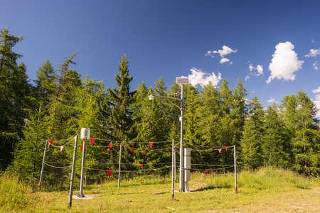 pluviometro: Estaci�n meteorol�gica en la alta altitud en los Alpes italianos, con bosques de alerce verde y el cielo azul Foto de archivo