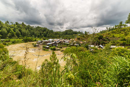 Traditional village on a river bank in the remote Mamasa Valley, West Tana Toraja, South Sulawesi, Indonesia. Wide angle view. photo
