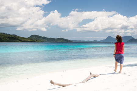 water s edge: Tourist watching the stunning colors of the remote Togean Islands, Central Sulawesi, Indonesia. Stock Photo