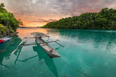 Breathtaking sunset and colorful traditional boat floating on blue lagoon in the Togean (or Togian) Islands, Central Sulawesi, Indonesia. Stock Photo