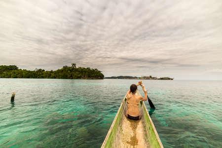 ocean kayak: Mujer remando turista en canoa tradicional de madera en laguna azul en las Islas Togean remotas, Sulawesi Central, Indonesia. Cielo dram�tico, �ngulo de visi�n trasera de ancho.