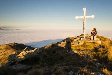 valley below: Female hiker reaching her goal at the mountain top and sitting near the summit cross with clouds on the valley below. Wide angle view at sunset. Stock Photo