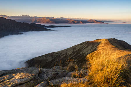 valley below: Stunning landscape at sunset on the italian western Alps with clouds covering the valley below. Stock Photo