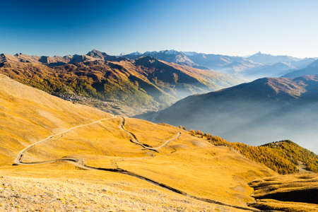 bardonecchia: Dirt mountain road crossing alpine slopes and colorful meadows in autumn season at sunset. Wide angle view of misty valley and mountain range in the background. Stock Photo
