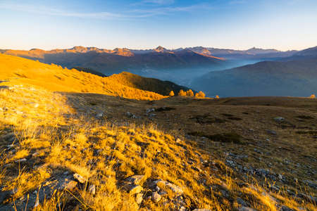 bardonecchia: Panoramic view of alpine misty valley and mountain range in a colorful autumn with yellow meadows and high mountain peaks in the background. Wide angle shot at sunset. Stock Photo