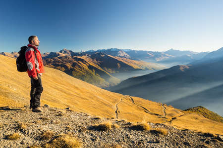 conquering adversity: Male hiker relaxing at sunset at the mountain summit and looking at majestic panorama of the italian Alps with dirt road crossing colorful meadows in autumn season and misty valley below.