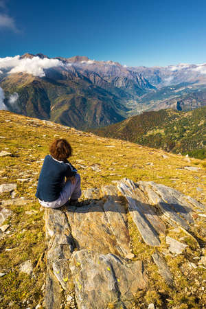 One person sitting on rock and looking at wide panoramic view of the valley below and high mountain range with autumnal colors. Italian Alps.