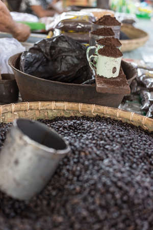 Selective focus on cups of ground roasted black coffee for sell in indonesian market (Sulawesi). photo