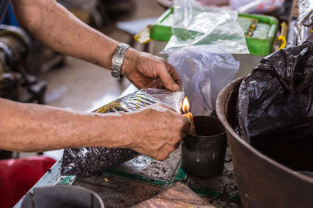 unrecognizable person: Market vendor sealing bag of freshly roasted black coffee beans for sell in indonesian market (Sulawesi). Unrecognizable person, arms and hands only shown.