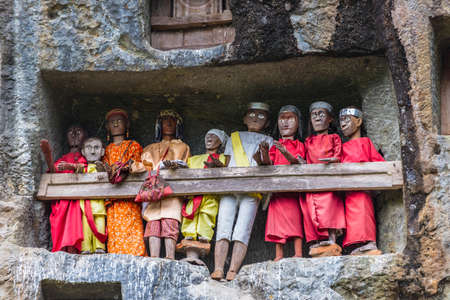 Londa (Tana Toraja, South Sulawesi, Indonesia), famous burial site with coffins placed in caves carved into the rock, guarded by balconies of dressed wooden statues, images of the dead persons (called tau tau in local language).