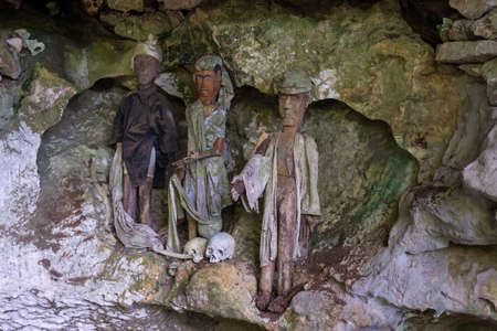 toraja: Tampangallo (Tana Toraja, South Sulawesi, Indonesia), traditional burial site where coffins are placed in caves or hanging from the cliff, guarded by balconies of dressed wooden statues, images of the dead persons (called tau tau in local language). Editorial