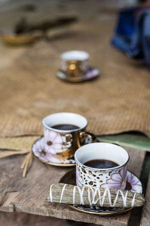 sulawesi: Selective focus on one of three cups of black coffee with traditional snack (sweet rice rolled inside palm leaf) on wooden bench. Sulawesi, Indonesia. Stock Photo
