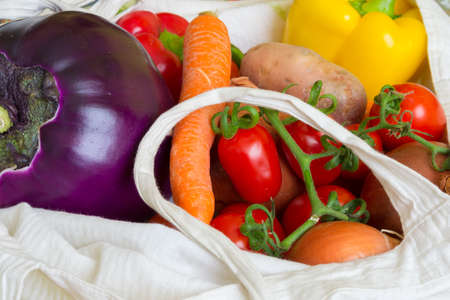 Close up of a cotton shopping bag full of fresh vegetarian food of different color for healthy eating. photo