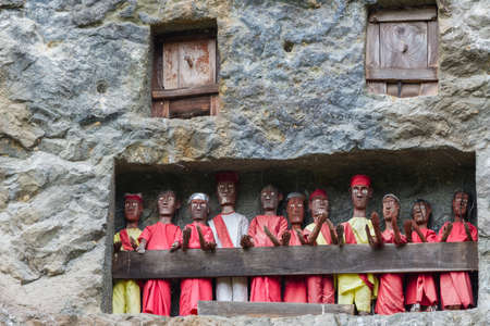 telephoto: Lemo (Tana Toraja, South Sulawesi, Indonesia), famous burial site with coffins Placed in caves carved into the rock, guarded by wooden balconies of dressed statues, images of the dead persons (called tau tau in local language). Details, telephoto view.