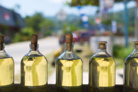 Selective focus on a row of glass bottles filled with transparent golden liquid, like engine oil, cooking oil, petrol, gasoline. photo