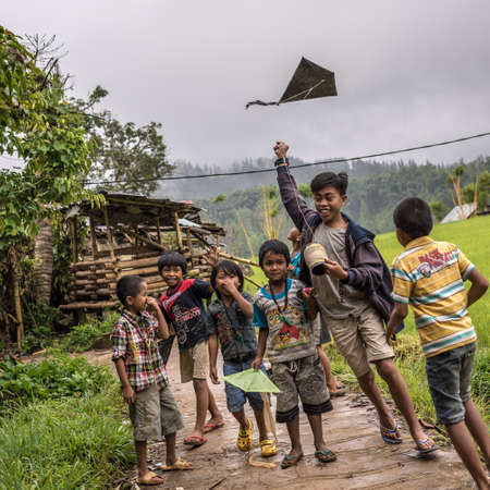 Mamasa, South Sulawesi, Indonesia - August 17, 2014: Local group of 6 children and 1 teen enjoying to play with kite in a cloudy rainy day.