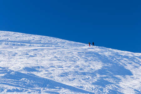 Couple of alpinists hiking uphill by back country ski on snowy slope in winter season. Italian Alps. Unrecognizable persons, minimal composition, clear blue sky.
