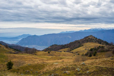 Autumnal landscape at sunset over alpine valley and snowcapped mountain range. Cold feeling, wide angle view from above. Italian Alps. photo