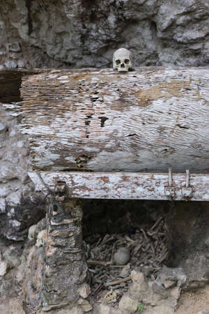 south asian ethnicity: Human bones and skulls in Ketekesu (Tana Toraja, South Sulawesi, Indonesia), traditional burial site with semi open old wooden coffins placed in caves or hanging from cliffs.