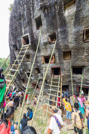 9 10 years: Lokomata, Indonesia - September 9, 2014: Open graves in a cliff with large group of local people attending the ceremony of cleaning corpses (Manene in local language), held once in every 5 or 10 years in Tana Toraja, South Sulawesi.