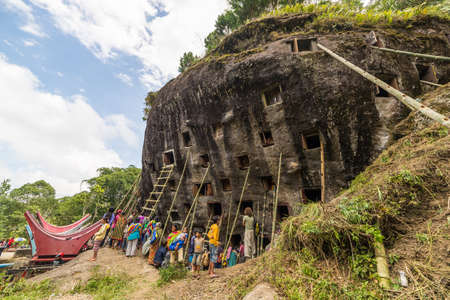 corpses: Lokomata, Indonesia - September 9, 2014: Open graves in a cliff with large group of local people attending the ceremony of cleaning corpses (Manene in local language), held once in every 5 or 10 years in Tana Toraja, South Sulawesi.