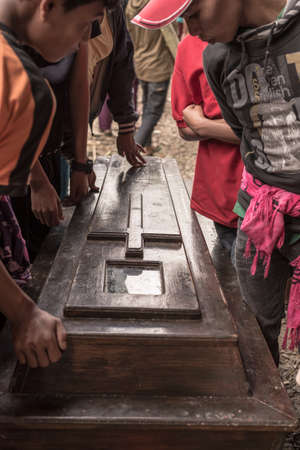 corpses: Lokomata, Indonesia - September 9, 2014: Local people opening coffin while attending the ceremony of cleaning corpses (Manene in local language), held once in every 5 or 10 years in Tana Toraja, South Sulawesi.