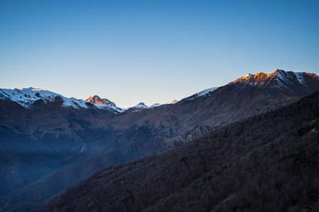 mountain valley: Last sunlight on the alpine arc with glowing peaks arising from the misty valley below. Aerial view on the Susa Valley, Torino Province, Italy.
