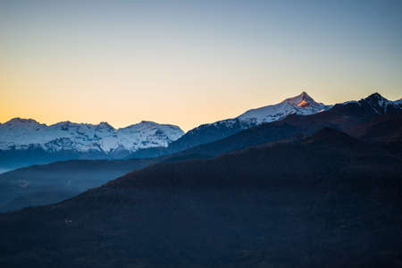 Last sunlight on the alpine arc with the glowing peak of M. Rocciamelone (3538 m) arising from the misty valley below. Aerial view on the Susa Valley, Torino Province, Italy.