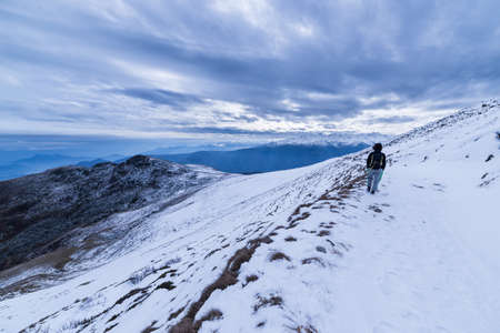 the one person: Winter landscape in the italian Alps. One person walking on frozen snow. Wide angle view at sunset, cold feeling and winter light. Stock Photo