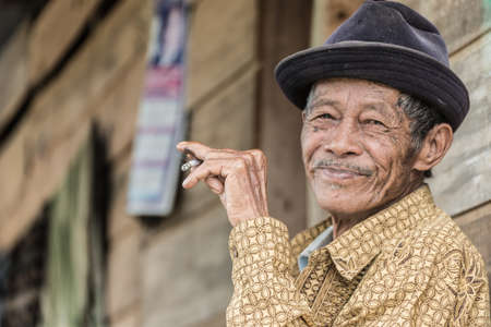 senior smoking: Osango, Sulawesi, Indonesia - August 17, 2014: Portrait of an unidentified senior man of Toraja ethnicity smoking a cigarette and smiling in Osango, Mamasa region, Sulawesi, Indonesia.