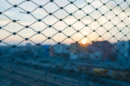 confined: Selective focus on metal fence in backlight at sunset. Blurred general cityscape in the background. Concept of trapping.