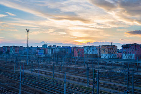 industry moody: Railway tracks and suburbs in Turin (Torino, Italy). View from above at sunset, with the majestic M. Viso peak arising in the background.