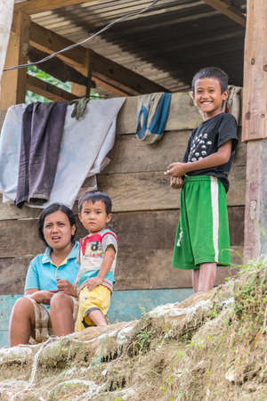 adult indonesia: Osango, Sulawesi, Indonesia - August 17, 2014: Two little boys with adult woman of Toraja ethnicity smiling while looking at the camera in the village of Osango, Mamasa region, West Tana Toraja, Sulawesi, Indonesia.