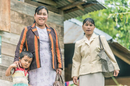 toraja: Osango, Sulawesi, Indonesia - August 17, 2014: Two women of Toraja ethnicity with little boy in the village of Osango, Mamasa region, West Tana Toraja, Sulawesi, Indonesia.