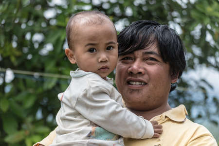 adult indonesia: Osango, Sulawesi, Indonesia - August 17, 2014: Young male adult holding his cute baby of Toraja ethnicity, in the village of Osango, Mamasa region, West Tana Toraja, Sulawesi, Indonesia. Editorial