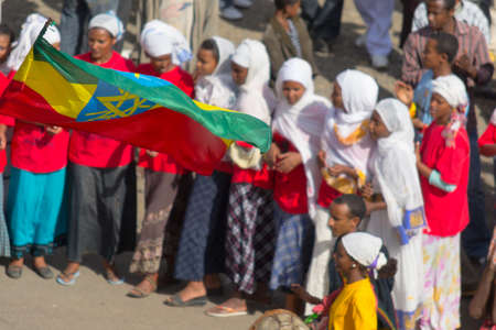 ethiopian ethnicity: Gonder, Ethiopia - January 19, 2012: national flag of Ethiopia and group of unidentified people dressed in traditional attire during the Timkat holiday, the important Ethiopian Orthodox celebration of Epiphany.