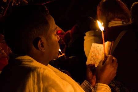 amharic: Gonder, Ethiopia - January 20, 2012: priest holding a candle in the night and reading a book written in the old language of the church, called Geez, during the Timkat holiday, the important Ethiopian Orthodox celebration of Epiphany.