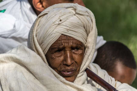 Gonder, Ethiopia - January 20, 2012: Portrait of old woman with traditional headscarf in the street of Gonder during the Timkat holiday, the important Ethiopian Orthodox celebration of Epiphany.