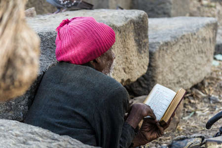 Lalibela, Ethiopia - January 23, 2012: Senior pilgrim reading a book written in the old language of the church, called Geez, during the Timkat holiday, the important Ethiopian Orthodox celebration of Epiphany.