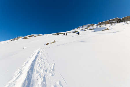 Group of tour skier hiking uphill on a steep snowy slope. Ski tracks in powder snow, clear blue sky, winter season. Unrecognizable people. photo