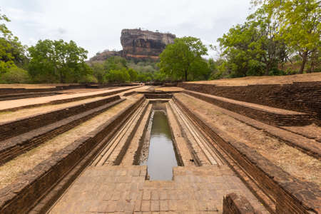 temple tank: Ancient water channel in direction of the majestic Sigiriya rock, the most important and famous archeological site and travel destination in Sri Lanka, Asia. Panoramic view from below. Editorial